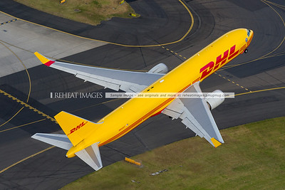 Polar Air Cargo DHL N644GT seen from the air at Sydney airport. Has commenced takeoff, and we are chasing it down the eastern side of the runway. N644GT is accelerating quickly away from us. No, we weren't from your company - but we were happy to photograph your plane.