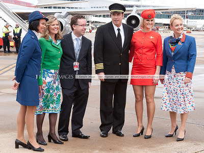 ohn Travolta and Qantas' Alan Joyce pose for the cameras with staff modelling the classic uniforms that represent the long history of Qantas.